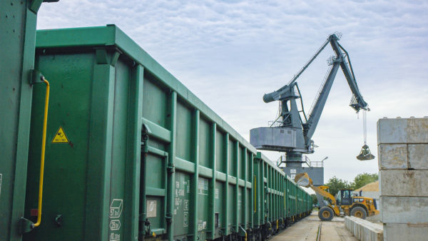 heeled loaders and port cranes load earths into green rail cars at bayernhafen Aschaffenburg