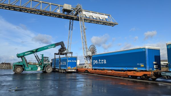 A reach stacker unloads a blue semi-trailer from a train and places it on a truck at bayernhafen Aschaffenburg