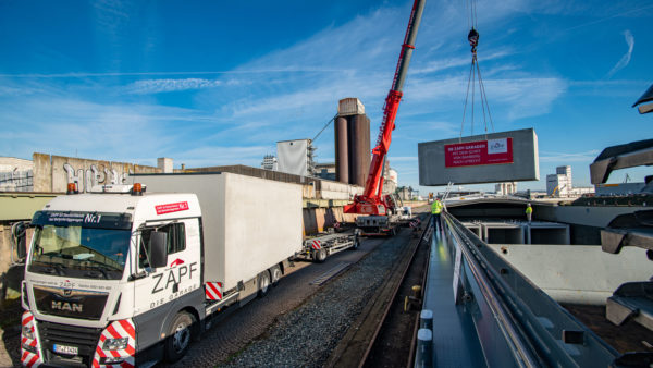 Loading of prefabricated concrete garages from trucks on to barge at bayernhafen Bamberg